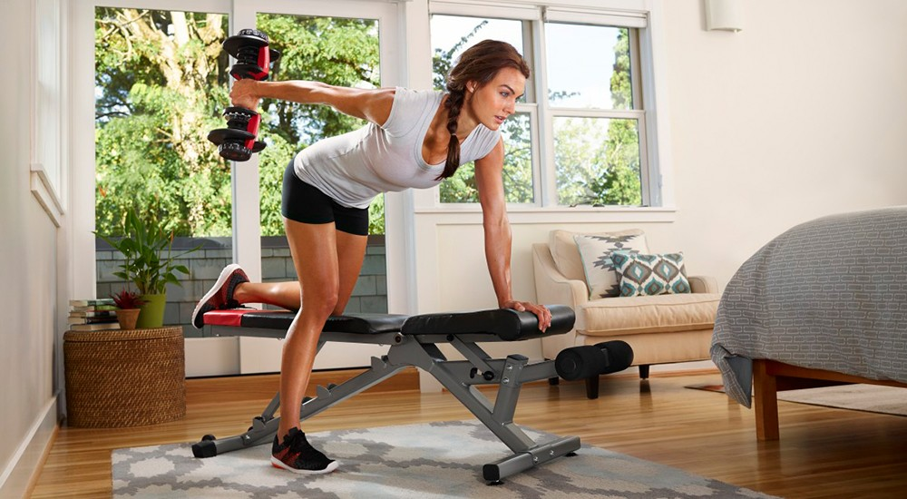 A woman working out in her home with weights