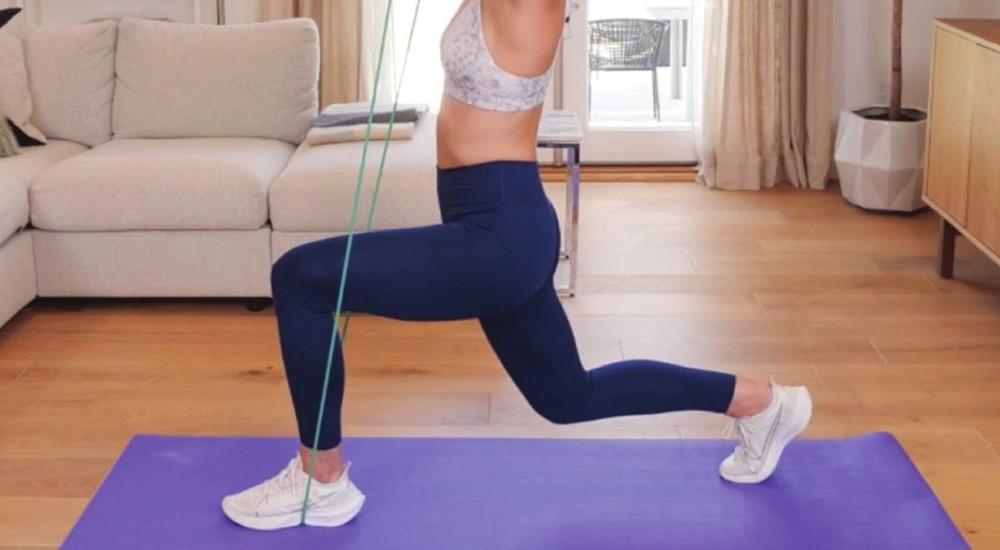 a woman using resistance bands while working out at home