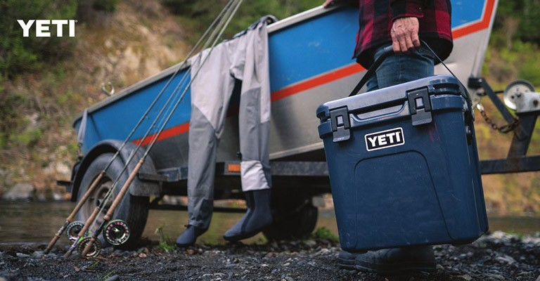 A fisherman using a yeti cooler for fishing