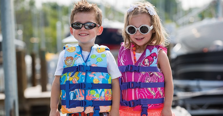 two kids in sunglasses wearing coast guard-approved life jackets