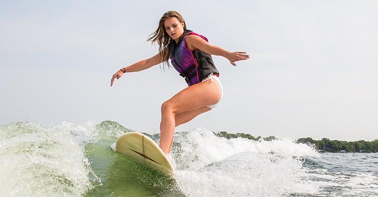 girl wake surfing with a neoprene life jacket