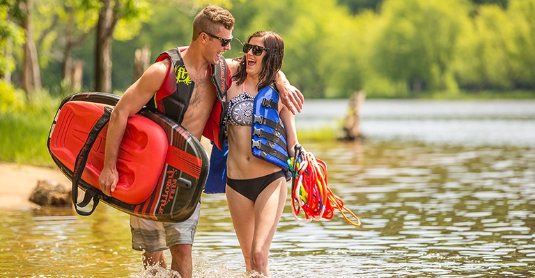 two people wearing life jackets on the beach while carrying water toys