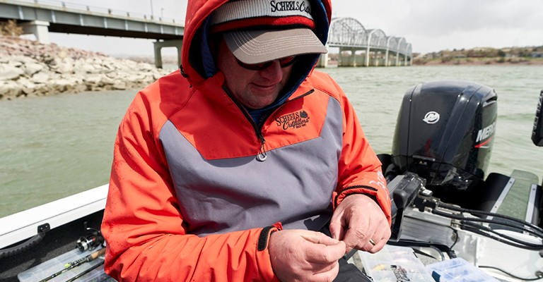 An angler wearing Scheels Outfitters fishing clothing