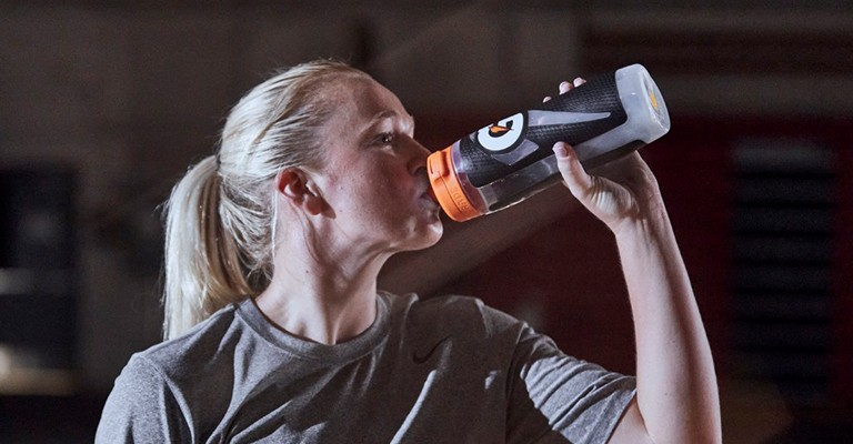 a volleyball player drinking from a water bottle