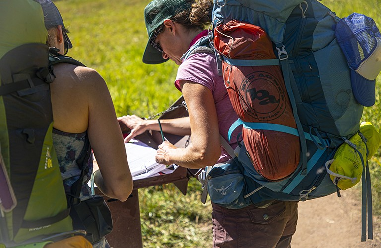 two people looking at a map while backpacking