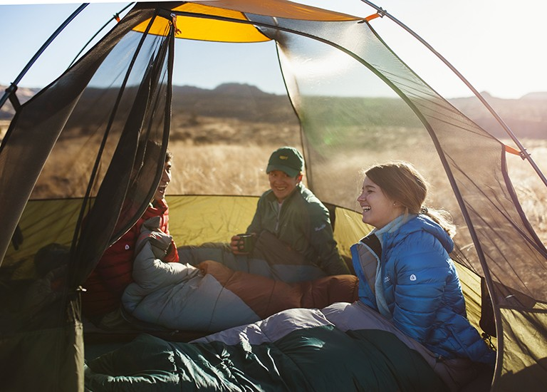 group of three people sitting in sleeping bags inside a tent and laughing