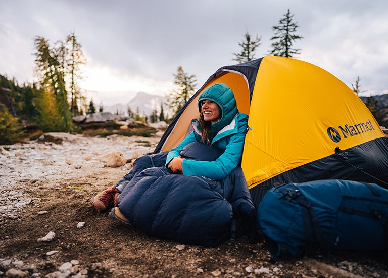 woman sitting at inside the door of a marmot tent with a sleeping bag wrapped around her legs as a blanket
