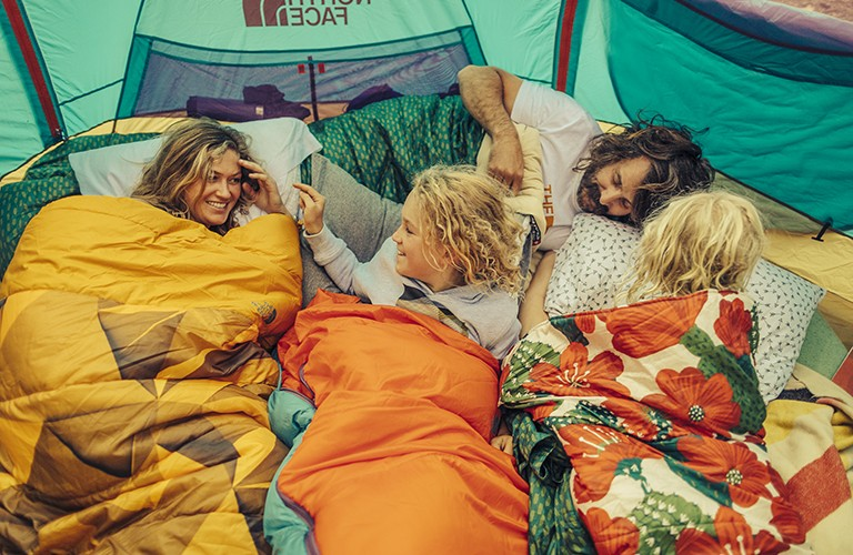 A family with two little girls laying inside sleeping bags inside a tent