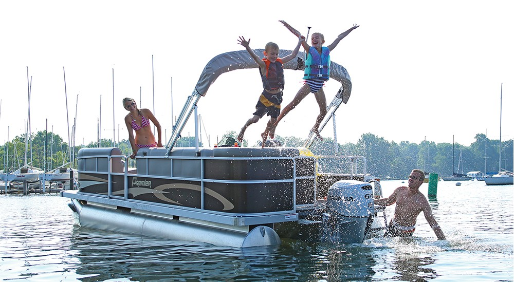 kids jumping off a pontoon with life jackets on