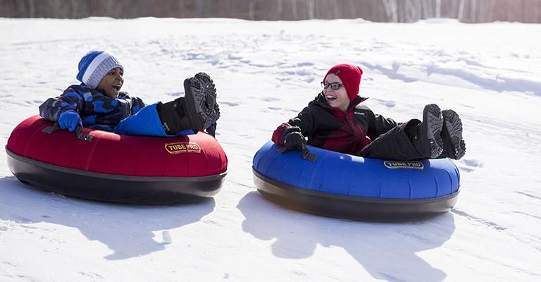 kids snow tubing down a hill