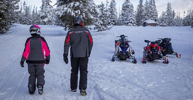people walking towards a snowmobile