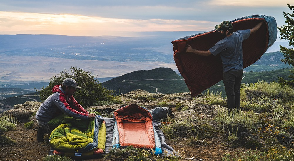 Two men setting up sleeping bags and sleeping pads on the ground overlooking a mountain