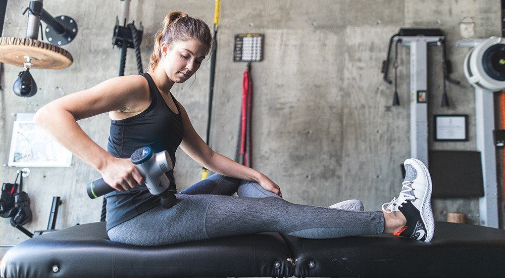 Girl using a percussion massager on her muscles